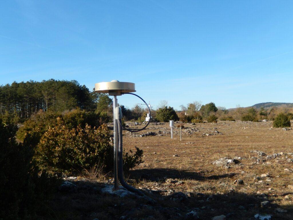 L'antenne GNSS sur un mât en acier inoxydable caché dans la roche sur le site de l'observatoire du Larzac (RENAG)